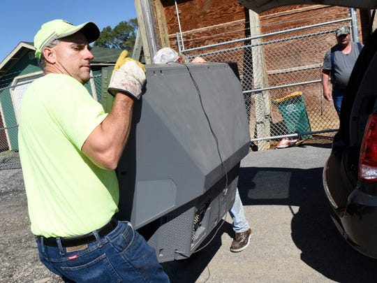 Mark Holtry carries a discarded TV during electronics drop-off at the borough dump off Hollywell Avenue, Chambersburg on Tuesday, Sept. 27, 2016. Chambersburg residents were mailed two tickets to bring electronics to the dump for recycling. The event lasts through Saturday.