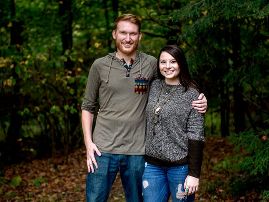 Will and Angela Bailey pose for a portrait in the woods