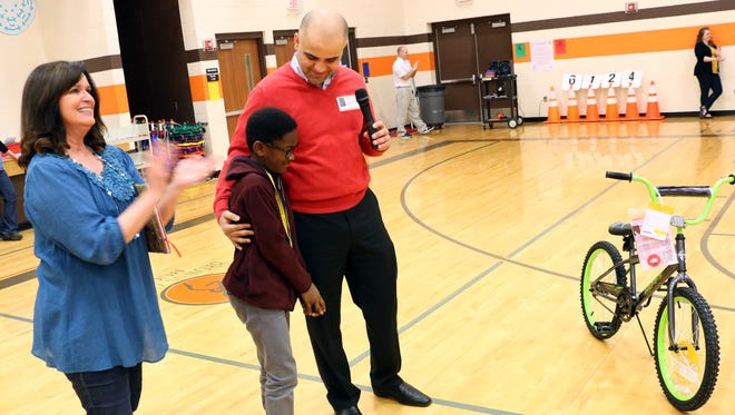 While Principal Kellye Goostree cheers with other students, Brown's Chapel Elementary School student Darren Boakye hugs Andy Obeissy — owner of Toyota and Scion of Murfreesboro and Ford of Murfreesboro — after Boakye was awarded a bike for maintaining perfect attendance. Boakye said he did not  have a bike at home.