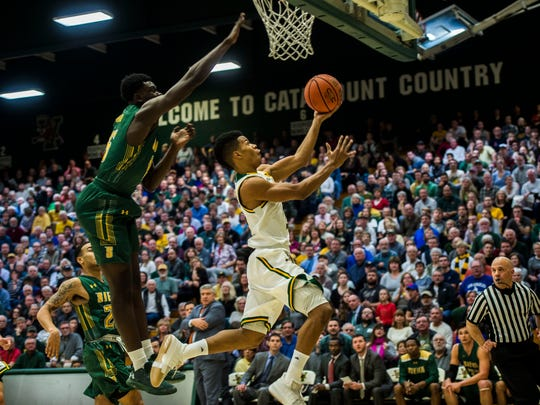 UVM's #2 Trae Bell-Haynes goes underneath, drawing the foul during their men's basketball game against Siena Monday night, Dec. 11, 2017, at Patrick Gym in Burlington. UVM won, 81-57.