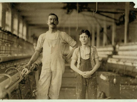 A mule-spinner and his assistant, Leopold Daigneau, at the Chace Cotton Mill in Burlington. Photo was taken in 1909.