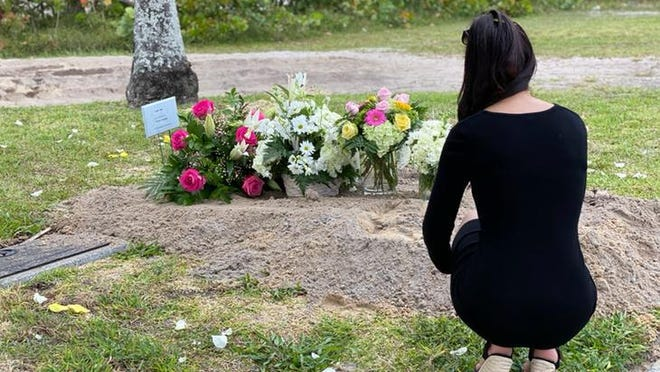 """Deniz Killic squats down next to her mother's graveside after her burial on April 5 near Lantana. Azade """"Azzie"""" Kilic, of Queens, NY, died from COVID-19 on April 2 in Delray Beach."""