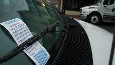A Wilmington parking ticket is left under the windshield wiper of a vehicle along Market Street. An ordinance under consideration by the City Council proposes lane direction and signage changes throughout the city.