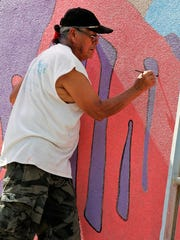 Artist James Joe adds a dark outline to part of his new mural on the east side of the Brown's Shoe Fit Co. in downtown Farmington.