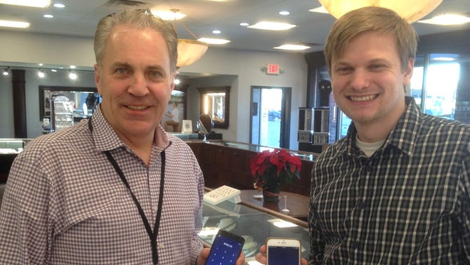 Dean Murray, owner of the The Jewelry Center, and Joe Kelnhofer, the chain's digital marketing director, show the app for converting sales to bitcoin at the The Jewelry Center in Greenfield. The Milwaukee-area chain is now accepting the cryptocurrency.
