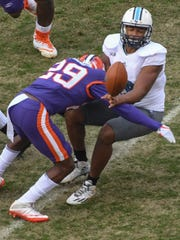 Clemson cornerback Marcus Edmond (29) hits The Citadel quarterback Jordan Black(10) as he pitches out during the first quarter in Memorial Stadium at Clemson on Saturday.