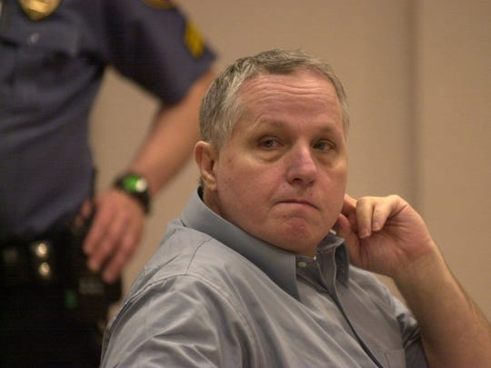 Murder defendant Robert Zarinsky glances towards the