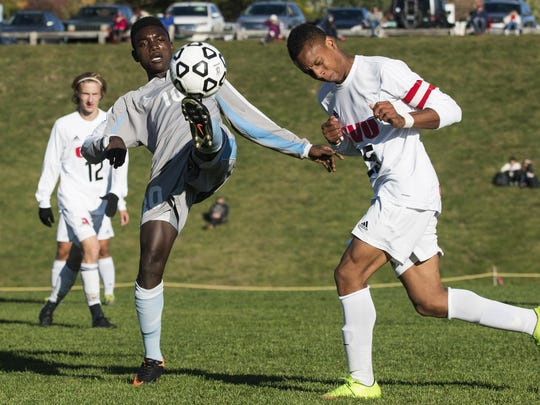 South Burlington's Amerlin Nemeye (10) kicks the ball in front of CVU's Trey Tomasi (25) during the high school boys soccer game between the South Burlington Rebels and the Champlain Valley Union Redhawks on Monday afternoon in Hinesburg.