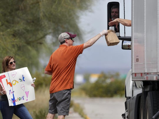 Chris Lyndberg and his wife Megan Lyndberg give free lunches last week to truck drivers at a rest area along I-10 in Sacaton, Ariz. The Arizona Trucking Association was giving away 500 lunches to truck drivers in appreciation for delivering necessities.