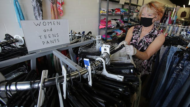 Linda Shaull, a volunteer at the Perry Helping Perry Clothes Closet, puts out pants that have been donated.