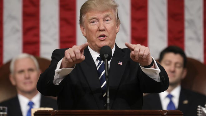 President Donald Trump addresses a joint session of Congress on Capitol Hill in Washington on Tuesday as Vice President Mike Pence and House Speaker Paul Ryan of Wis., listen.