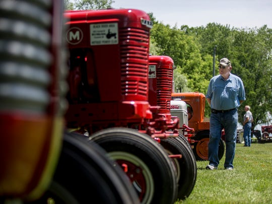 Jerry Norris, of Yale, walks along a row of Farmall tractors during an antique tractor show Saturday, June 18, 2016 in Lexington.