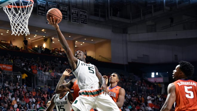 Miami Hurricanes guard Davon Reed (5) drives to the basket as Clemson Tigers forward Jaron Blossomgame (5) looks on during the second half at Watsco Center in Coral Gables, Fla.