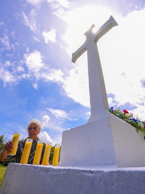 World War II survivor Julia Manley Villagomez places a lit candle next to others at the base of a cross during a memorial service at the Old Agat Cemetery on Thursday, July 19, 2018. The candles were presented to remember the dozens of Chamoru men and women massacred at the Fena Cave by Imperial Japanese Forces during the liberation of the island in World War II.