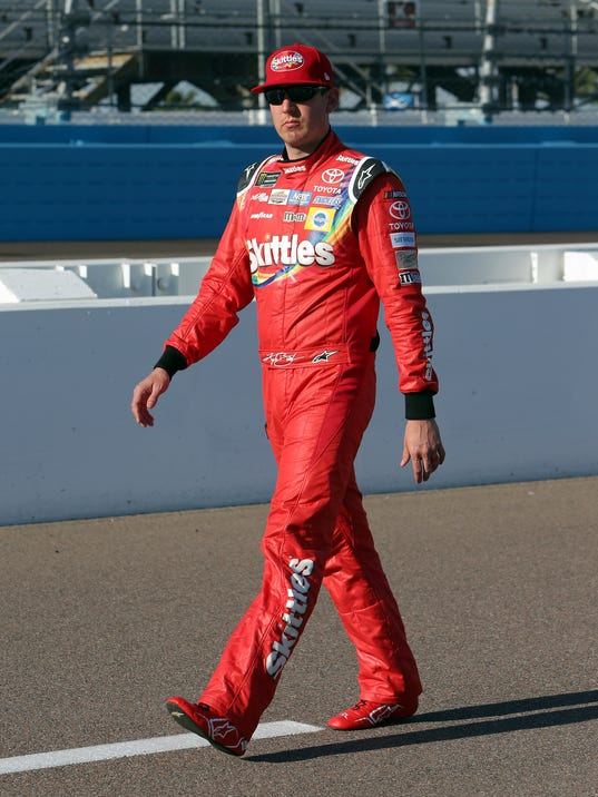 Kyle Busch walks along pit road before qualifying for Sunday's NASCAR Cup Series auto race, Friday, March 17, 2017, in Avondale, Ariz. (AP Photo/Rick Scuteri)
