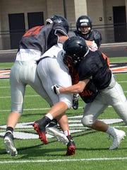 A pair of Brighton tacklers stop a Linden runner during