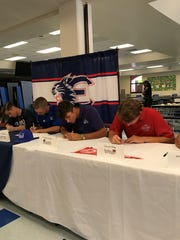 Estero's Christian Gorski (soccer, Nova Southeastern), Spencer Stegemann (baseball, Daytona State), Tommy Joesph (baseball, FSW) and Carson King (baseball, Florida Southern) sign their letters of intent at a signing day ceremony on Wednesday.