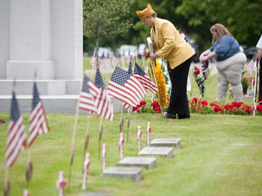 Lori Barber lays a wreath for the Forty and Eight Veterans Organization during Lansing's Memorial Day Service on May 28, 2016 at Evergreen Cemetery.