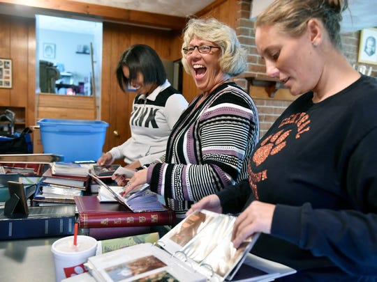 From left, Deoza Sweeney, Martiann Landis and Brandi Landis sort through photo albums in preparation for Tom Landis Jr.'s funeral Wednesday, Oct. 18, 2017, in Manchester Township. Sweeney is a great-granddaughter of Tom Landis Jr.'s, while Martiann Landis is one of his daughters-in-law and Brandi Landis is one of his granddaughters and Sweeney's mother. Tom Landis Jr., who began serving with the York City Department of Fire/Rescue Services in 1957 and was chief from 1995 to 1998 before retiring, died Sunday, Oct. 15, 2017, at age 86. Landis was also the third of four generations of York City firefighters.