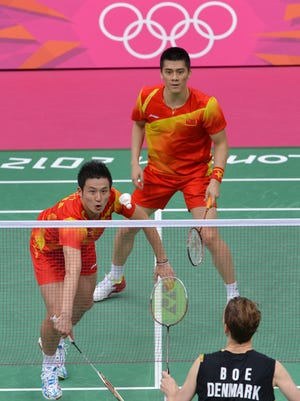 China's Cai Yun (L) and Fu Haifeng (R) play against Denmark's Mathias Boe and Carsten Mogensen in the Men's Doubles badminton gold medal match at the London 2012 Olympic Games in London, on August 5, 2012. AFP PHOTO / ADEK BERRY        (Photo credit should read ADEK BERRY/AFP/GettyImages)