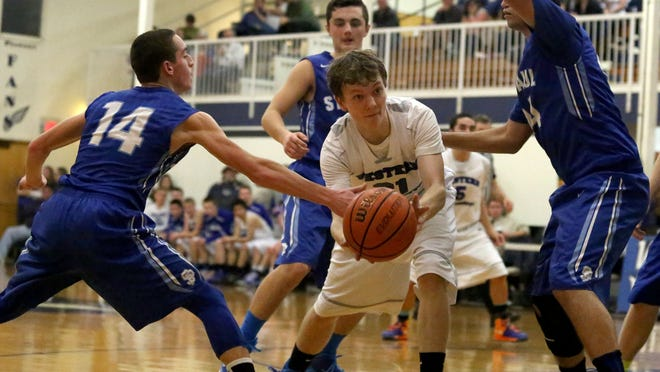 Western Mennonite's Jacobe DeJong, center, looks for a pass under pressure from St. Paul's Ryan Soumokil (14) during their Tri-River Conference game on Monday, Feb. 9.