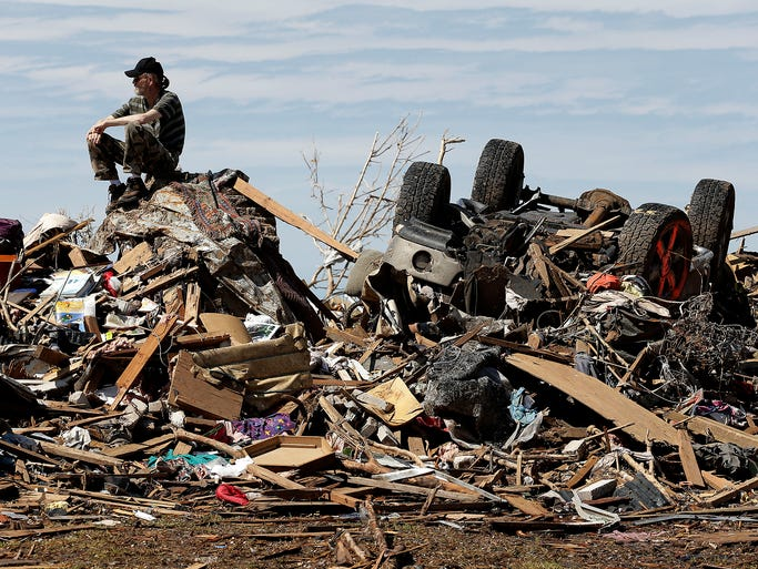David Lee Estep sits on a pile of rubble that was the home he shared with his parents after a powerful tornado tore through his community on May 23, 2013, in Moore, Okla. The EF5 tornado roared through the Oklahoma City suburb, flattening a wide swath of homes and businesses.