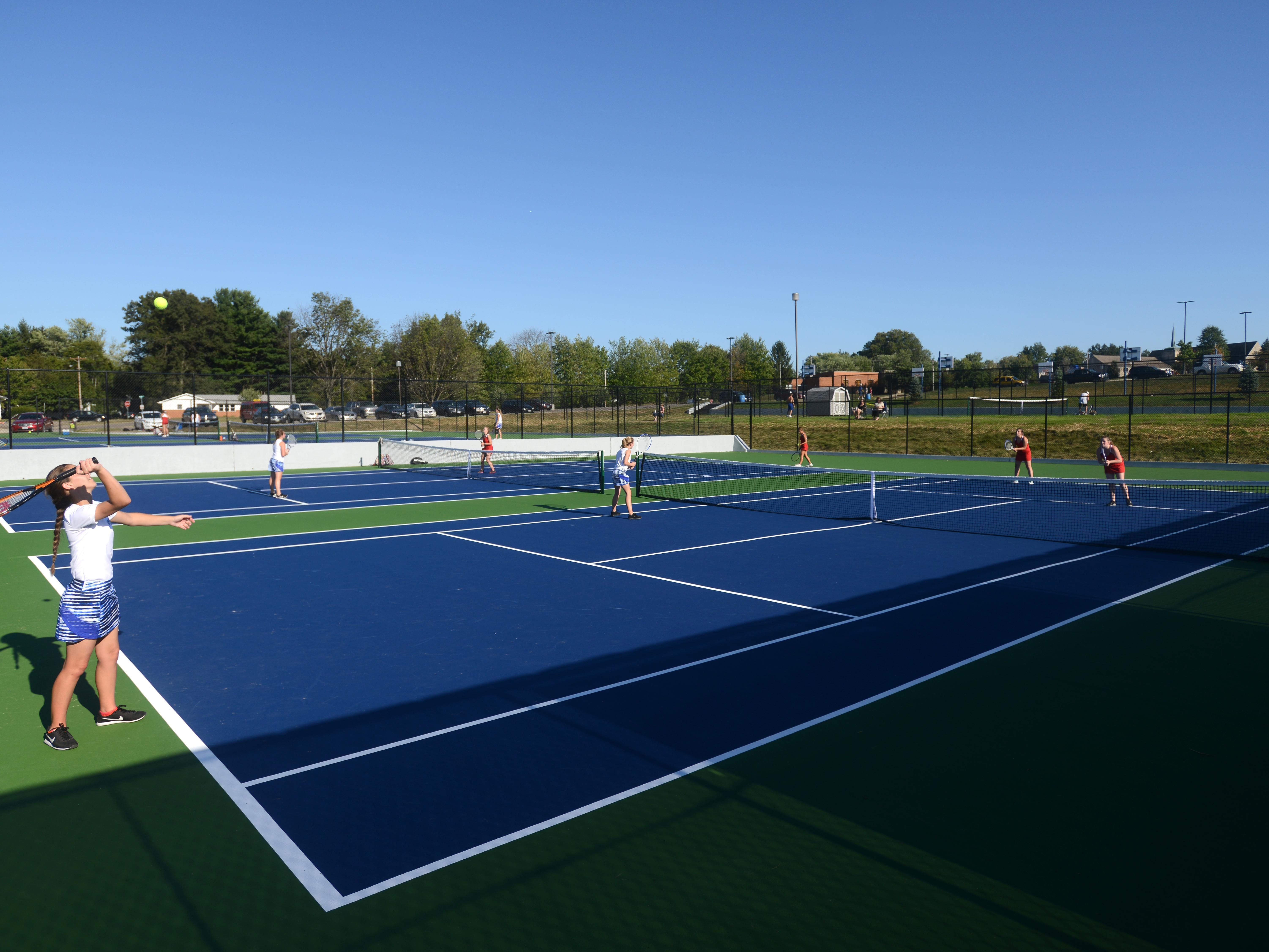 Zanesville's Madison Updegrave serves during a recent match with New Philadelphia. Zanesville High School unveiled its new tennis courts recently.