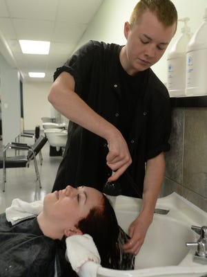 Natalie Runyon has her hair rinsed by Collin Erdosy at PJ's College of Cosmetology Thursday, Oct. 15, 2015, in Richmond.