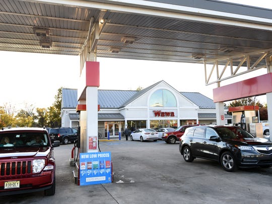 Customers at a Wawa gas station. Fuel prices are the lowest they've been all year.