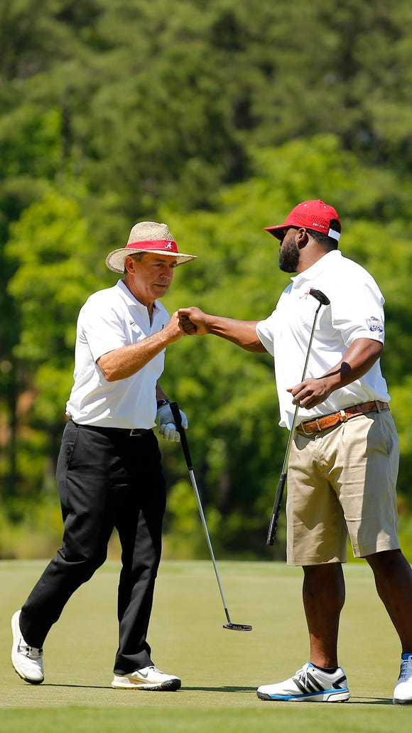 Alabama's Nick Saban, left, and Mark Ingram fist bump after a putt during the 2015 Chick-fil-A Peach Bowl Challenge Round on the Oconee Course at Reynolds Plantation on Tuesday, April 28, 2015.
