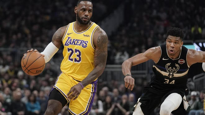 Los Angeles Lakers' LeBron James dribbles past Milwaukee Bucks' Giannis Antetokounmpo during the first half of an NBA basketball game Thursday, Dec. 19, 2019, in Milwaukee.