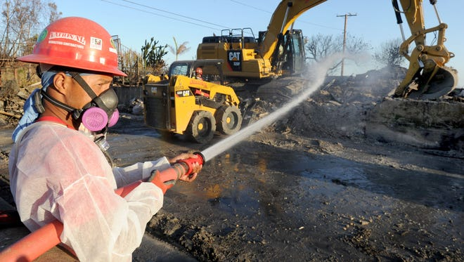 Johnny Trejo, with National Demolition Contractors, sprays water as the company demolishes a house around Via Ondulando in Ventura. The neighborhood is part of the Thomas Fire burn area.