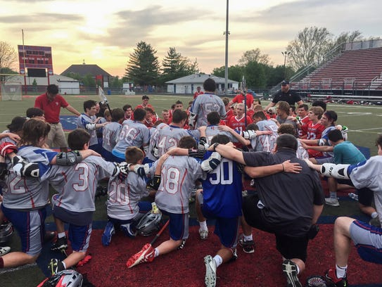 The Roncalli Rebels and Center Grove Trojans boys lacrosse teams pray together after a game on May 11, which had been rescheduled after assistant coach Vinny Romano had a heart attack and was revived on the field during a game on April 24. At center, Romano's son Vinny Romano (52) thanks the Trojans and his own teammates
