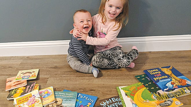 Young readers 10-month-old Kiptyn (left) and three-year-old Lennyn (right) Klein pose with some of the books they've gotten from Dolly Parton's Imagination Library.