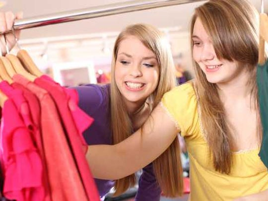 Two young women shop for clothes.