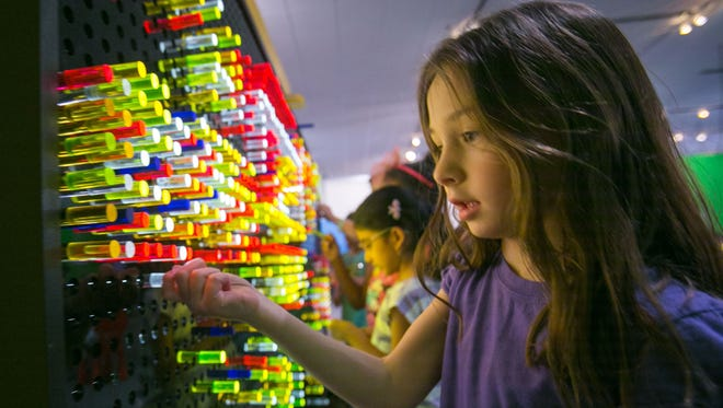 Sydney Younce interacts with a light exhibit at the i.d.e.a. museum in Mesa.