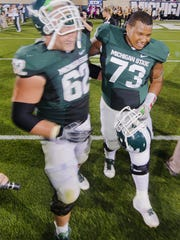 Arthur Ray Jr. (73) of MSU is congratulated by teammate Chris McDonald after playing in his first game as a Spartan after their season opening win over Youngstown State Friday September 2, 2011 in East Lansing.  Ray was diagnosed with leg cancer soon after signing with MSU and had never played a college game but started at left guard Friday night against Youngstown State.  Ray got the call after senior Joel Foreman asked the coaching staff to let Ray take his place. KEVIN W. FOWLER PHOTO