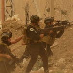 Security forces defend their headquarters against attacks by Islamic State extremists in Ramadi on May 14.