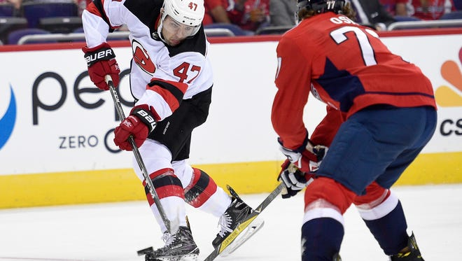 New Jersey Devils center John Quenneville (47) shoots the puck as Washington Capitals right wing T.J. Oshie (77) defends during the first period of an NHL preseason hockey game, Wednesday, Sept. 27, 2017, in Washington. (AP Photo/Nick Wass)