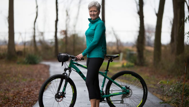 Anna Touchard wears a teal Nike three-quarter zip-upjacket, black Nike spandex capri running pants and Asics Trail running shoes in teal, orange and black.