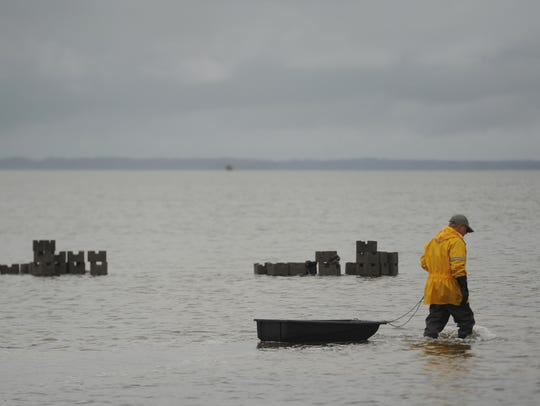 A volunteer wades by piles of concrete blocks used