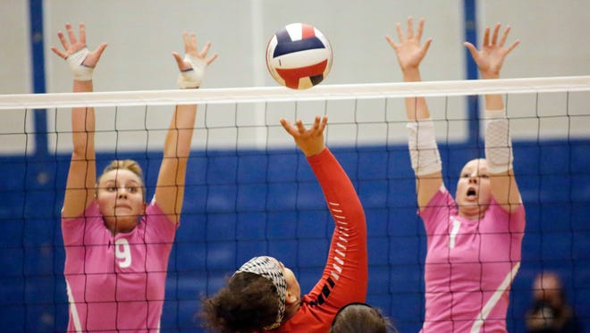 Manitowoc Lincoln's Kamryn Boyd (18) prepares to hit the ball to Sheboygan North's Kasey Bell (9) and Lauren Spaulding (1) Thursday October 5, 2017 in Sheboygan, Wis.