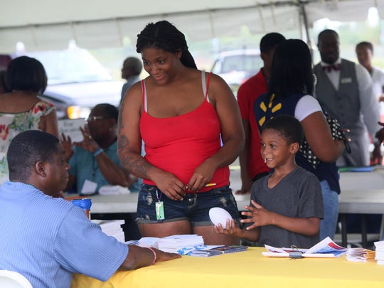 Rosalie Jones visits the Delaware HIV Consortium with 6-year-old Jeran Taylor while attending Wilmington Housing Authority's  empowerment fair at Kingswood Community Center on Wednesday.