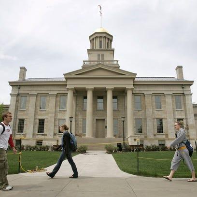 University of Iowa students walk past the Old Capitol building in Iowa City, Iowa.