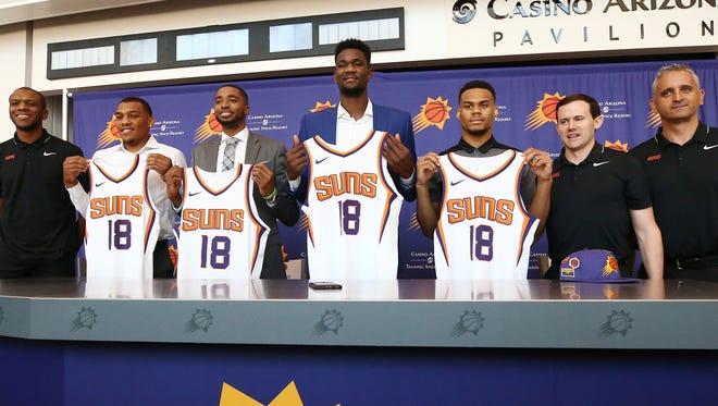 Phoenix Suns GM Ryan McDonough and head coach Igor Kokoskov (right) introduce his new players: George King (left), Mikal Bridges, Deandre Ayton and Elie Okobo on June 22, 2018, at Talking Stick Resort Arena in Phoenix, Ariz.