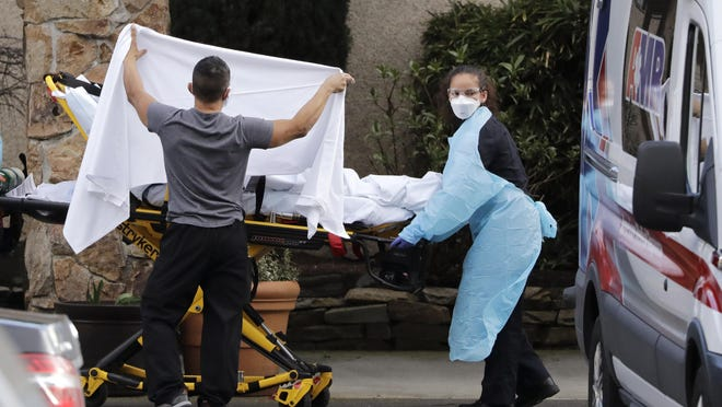 A staff member blocks the view as a person is taken by a stretcher to a waiting ambulance from a nursing facility where more than 50 people are sick and being tested for the COVID-19 virus in Kirkland, Wash.