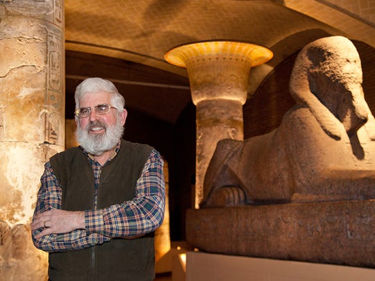 Patrick McGovern in the Lower Egyptian Gallery of the Penn Museum, with the largest sphinx in the Western hemisphere to his side and columns of the 13th-century B.C. Merenptah palace behind him.