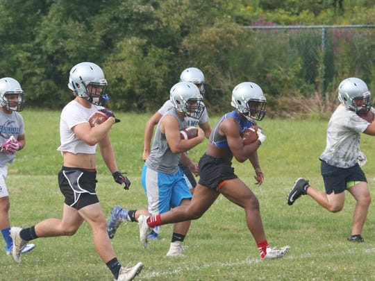 John Jay football players run a drill on the first day of practice at John Jay High School in Wiccopee on Monday.