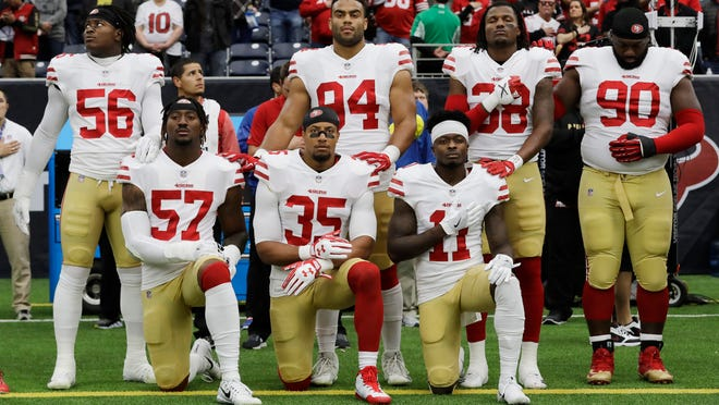 In this Dec. 10, 2017, photo, San Francisco 49ers' Eli Harold (57), Eric Reid (35) and Marquise Goodwin (11) kneel during the national anthem before an NFL football game against the Houston Texans, in Houston.