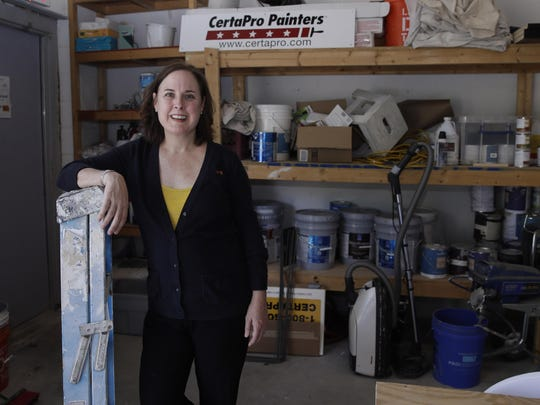Paige NeJame, who along with her husband owns a CertaPro painting franchise, poses in a work room at her company headquarters in Rockland, Mass.